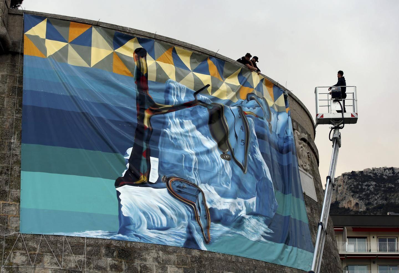 Accrochage de la fresque sur une bâche de 12mx7m du street artiste Eduardo Kobra sur le fort Antoine.