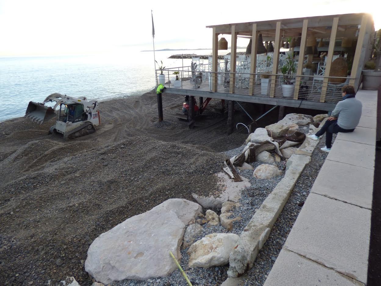 Un bulldozer enlève l'amas de galets charriés par la mer à La Spiaggia, à Cagnes.
