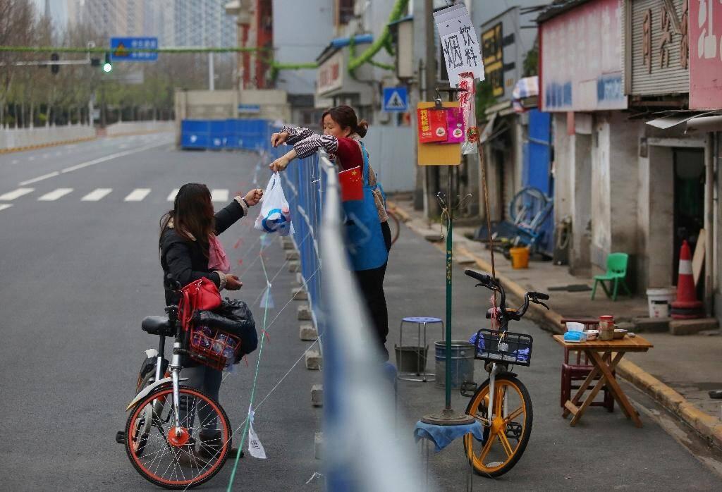 Livraison de nourriture par-dessus une barrière, le 16 mars 2020 à Wuhan, pendant l'épidémie du nouveau coronavirus