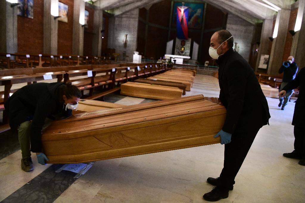 Des employés des pompes-funèbres apportent des cercueils dans l'église de San Giuseppe à Seriate, près de Bergame, le 26 mars 2020