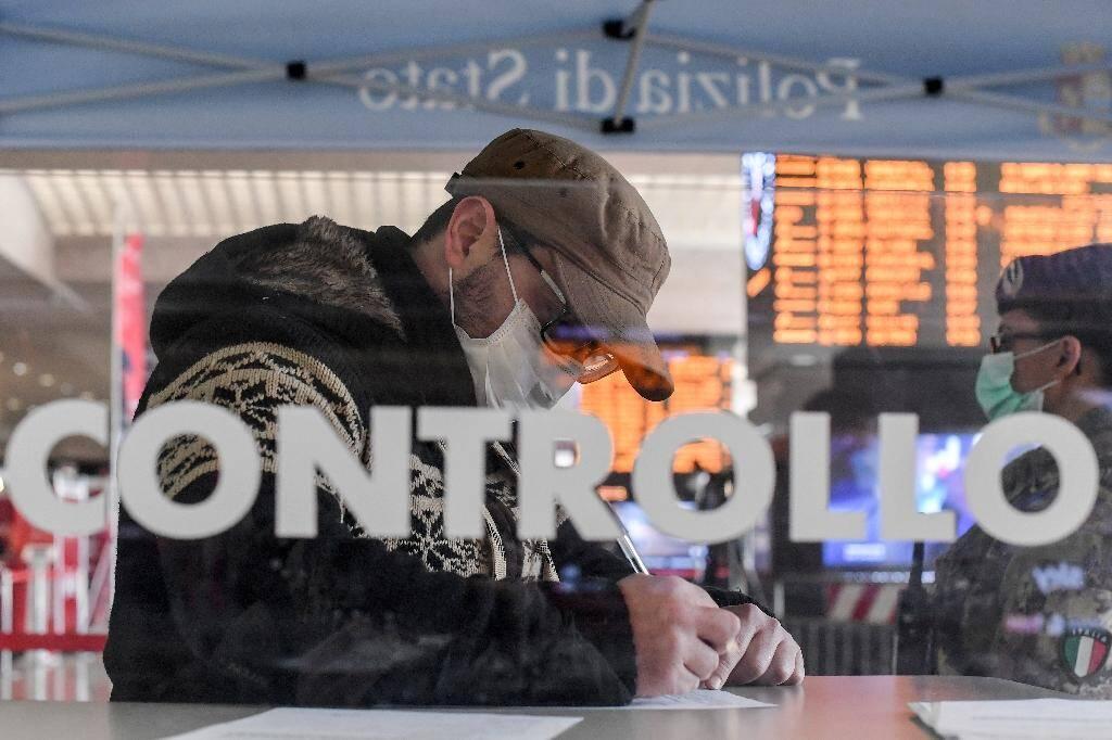 Un homme portant un masque remplit un formulaire à la gare Termini de Rome à côté d'une soldate portant elle aussi un masque, le 10 mars 2020.