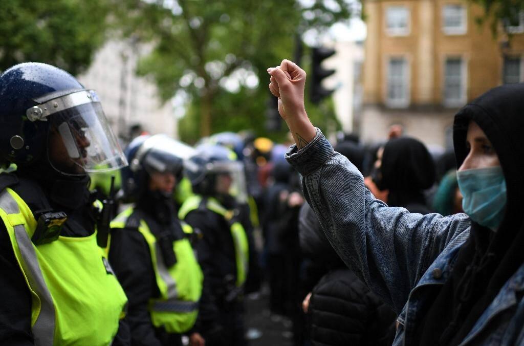 Un manifestant portant un, masquez fait face à des policiers lors d'une manifestation contre le racisme à Londres le 6 juin 2020