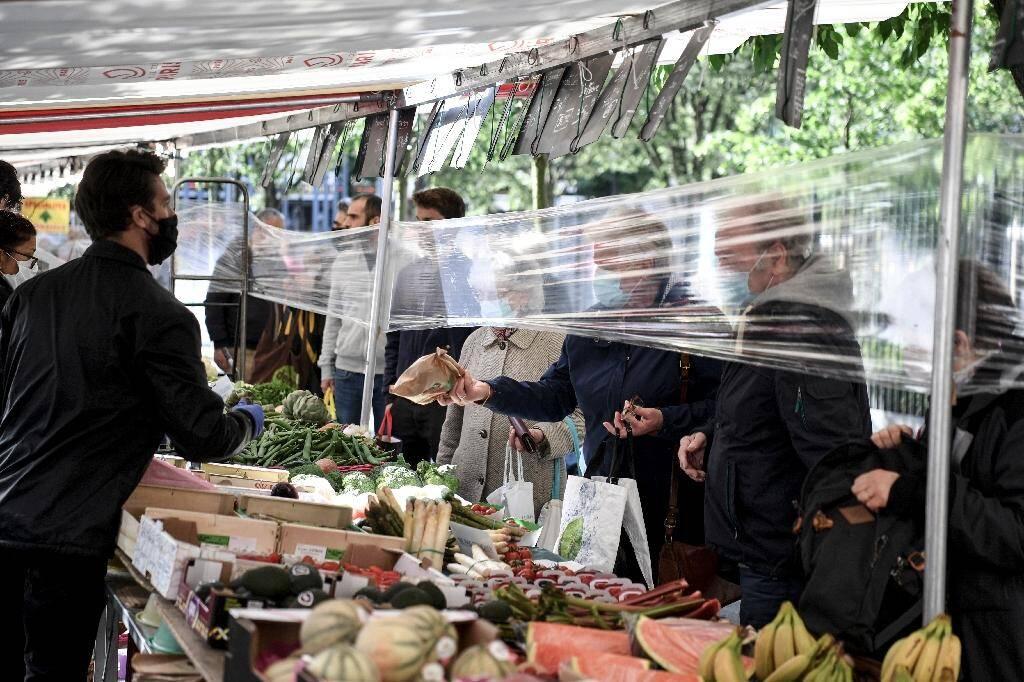 Un film plastique entre des clients et des vendeurs de fruits et légumes sur un marché à Paris en mai 2020