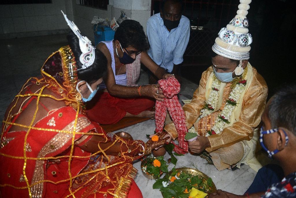 Un prêtre hindou effectue des rituels pour un couple nouvellement marié alors qu'ils portent des masques dans un temple hindou à Siliguri le 28 juillet 2020