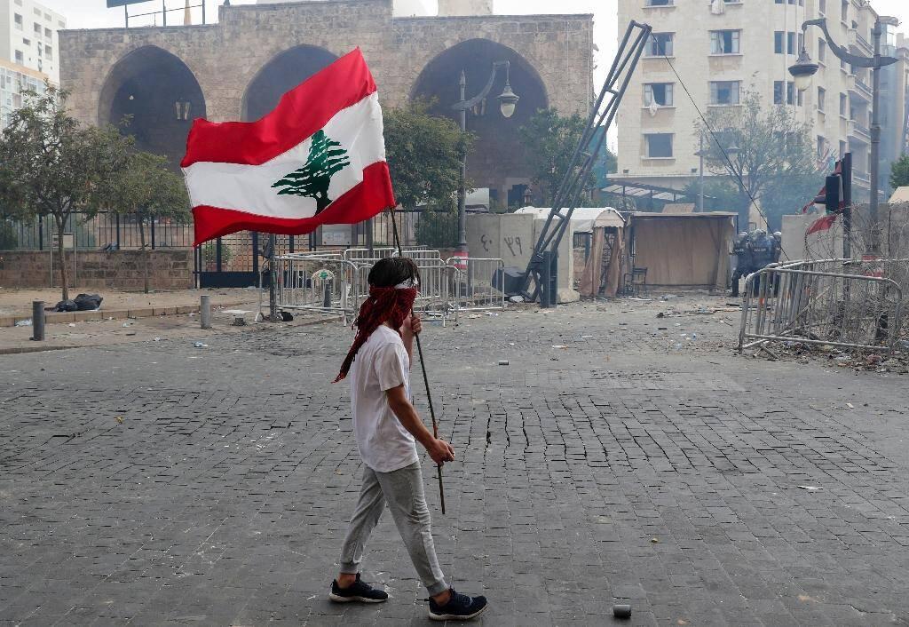 Un homme porte un drapeau libanais lors d'une manifestation, le 8 août 2020 à Beyrouth, pour demander des comptes à la classe politique après la terrible explosion ayant dévasté une partie de la capitale et fait plus de 150 morts