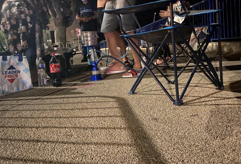 Chichas, fauteuils pliants: une famille s'est installée dans la largeur de la promenade piétonne, et discute tranquillement, à 1h30 du matin.