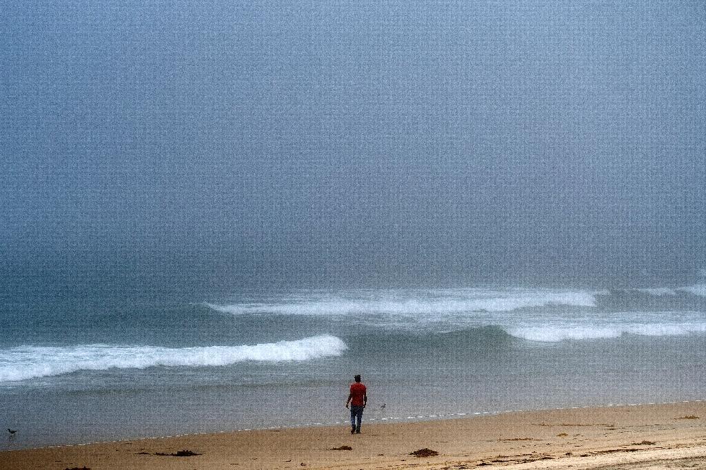 Un homme marche sur la plage de Tijuana, Etat de Baja California state, Mexique, le 2 ao^t 2020