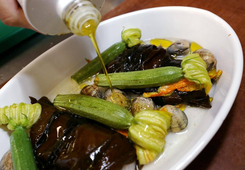 La sériole, un poisson de Méditerranée, a été emballée dans des algues, assaisonnée à l'huile d'olive et aux palourdes.