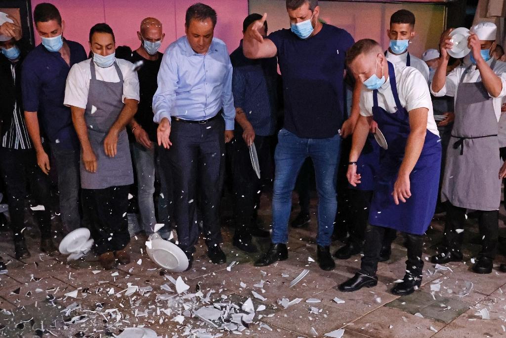 Des travailleurs du secteur de la restauration cassent des assiettes pour protester contre le nouveau confinement en Israël, le 15 septembre 2020 à Tel Aviv