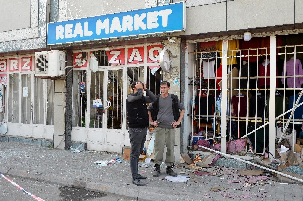 Deux hommes devant un magasin qui a subi des destructions après des tirs de missiles à Barda, le 28 octobre 2020