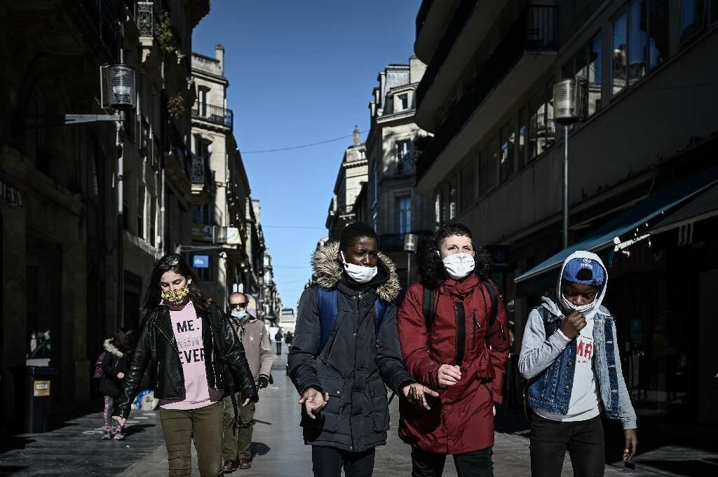 Passants devant des commerces fermés d'une rue de Bordeaux (sud-ouest de la France), le 5 novembre 2020.