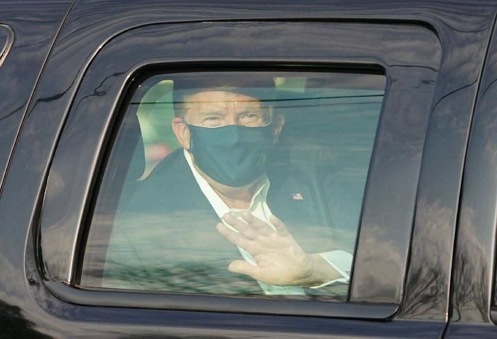 Le président américain Donald Trump salue ses symathisants depuis la limousine présidentielle lors d'une brève sortie de l'hôpital militaire de Walter Reed à Bethesda, près de Washington, le 4 octobre 2020