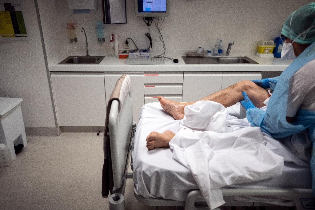 Une infirmière s'occupe d'un patient atteint du Covid dans une clinique au Muret, près de Toulouse le 16 novembre 2020