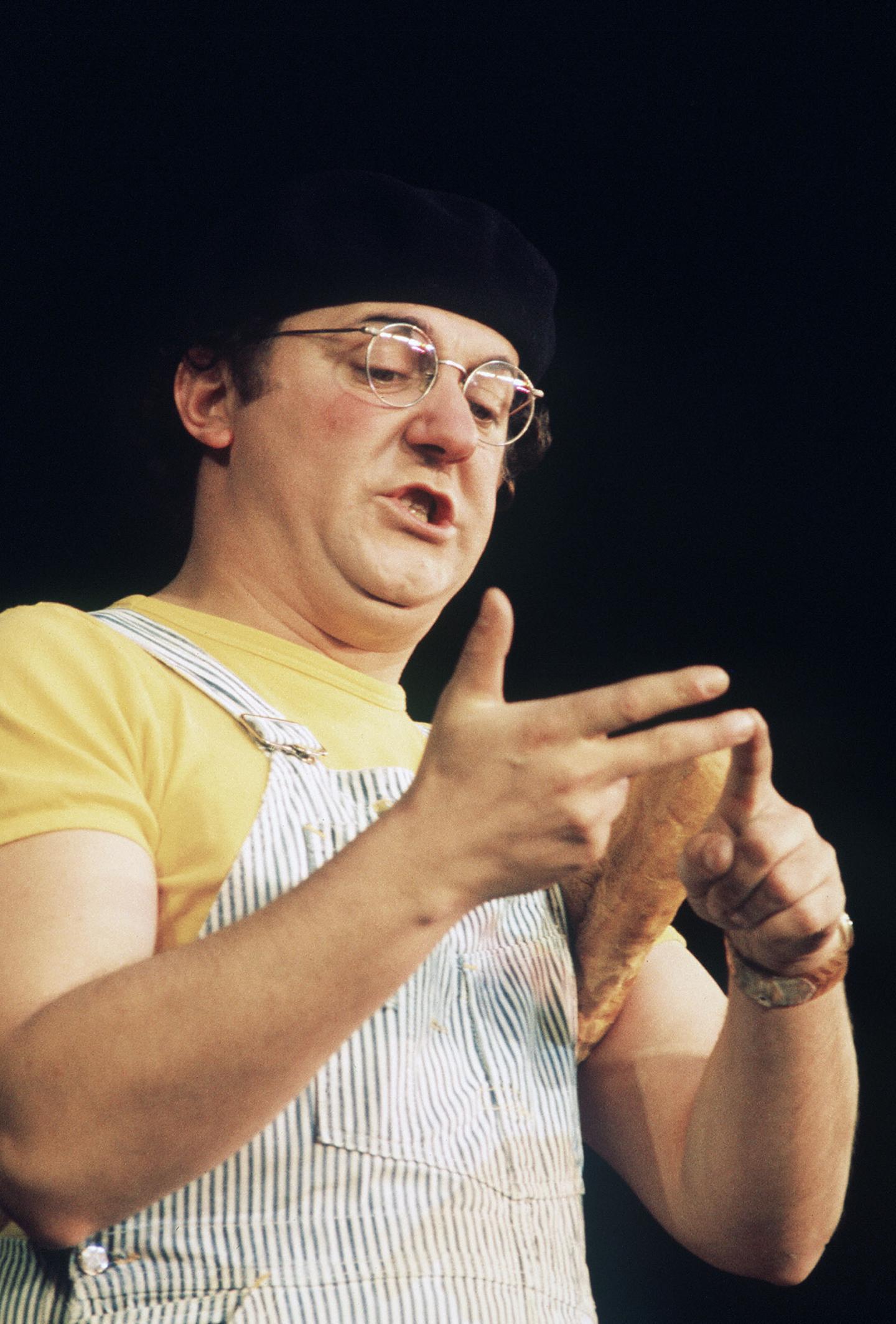 Le chansonnier-fantaisiste Coluche, vêtu de sa traditionnelle salopette rayée sur T-shirt jaune.