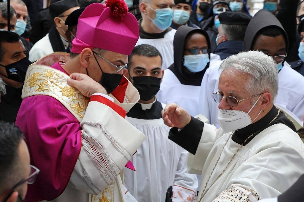 Le patriarche latin de Jérusalem Pierbattista Pizzaballa (g) arrive à la Basilique de la Nativité à Bethléem, le 24 décembre 2020