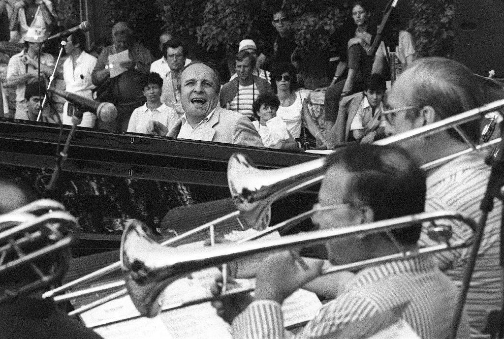 """Le pianiste de jazz français Claude Bolling (C) accompagne le 16 juillet 1983 le """"Big Band"""" lors de la 10e édition de la Grande Parade du Jazz de Nice"""