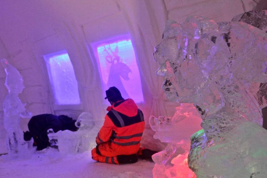 Un employé apporte la touche finale à une pièce du Arctic Snow Hotel, un hôtel fait de glace, le 17 décembre 2020 à Rovaniemi, en Laponie finlandaise
