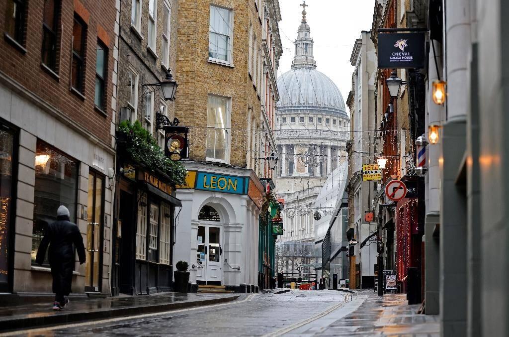 Une personne marche dans une rue de Londres rendue déserte par le confinement, le 5 janvier 2021