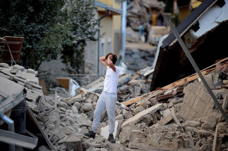 Un homme se tient debout au milieu des bâtiments totalement détruits à Amatrice.