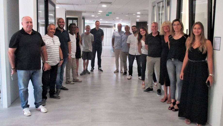 Les nouveaux employés posent fièrement aux côtés du directeur, dans les nouveaux locaux.