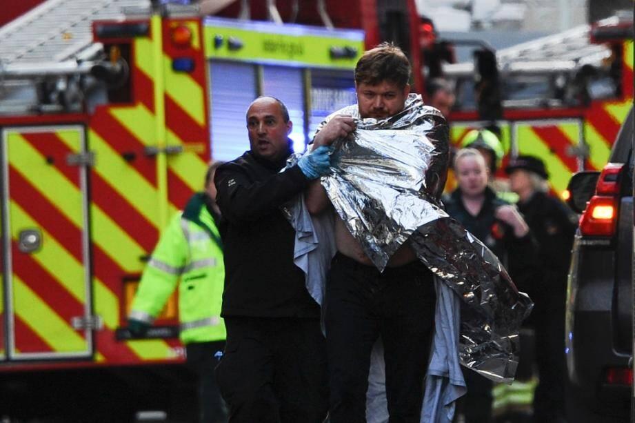 Un policier aide un homme blessé près du London Bridge, le 29 novembre 2019 à Londres