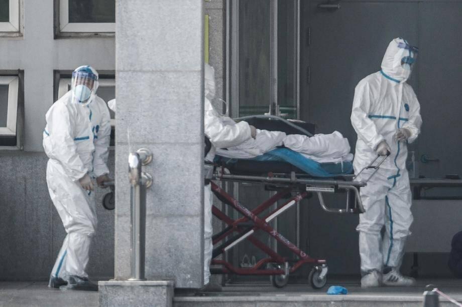 Des agents sanitaires transportent un malade dans un hôpital où sont soignés des patients infectés par un mystérieux virus analogue au Sras, le 18 janvier 2020 à Wuhan, en Chine