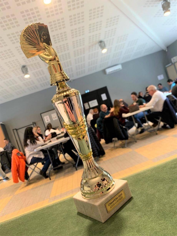 Le trophée du premier festival de belote contrée exposé dans la salle de jeu.