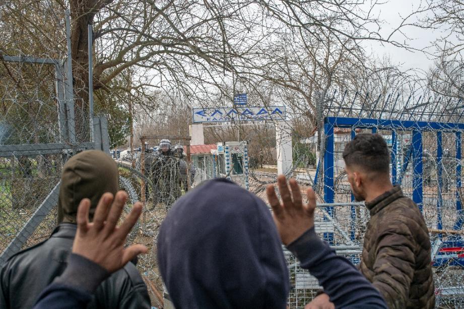 Des migrants s'adressent à la police grecque près du passage de la frontière entre la Turquie et la Grèce dans la région de Edirne, le 4 mars 2020