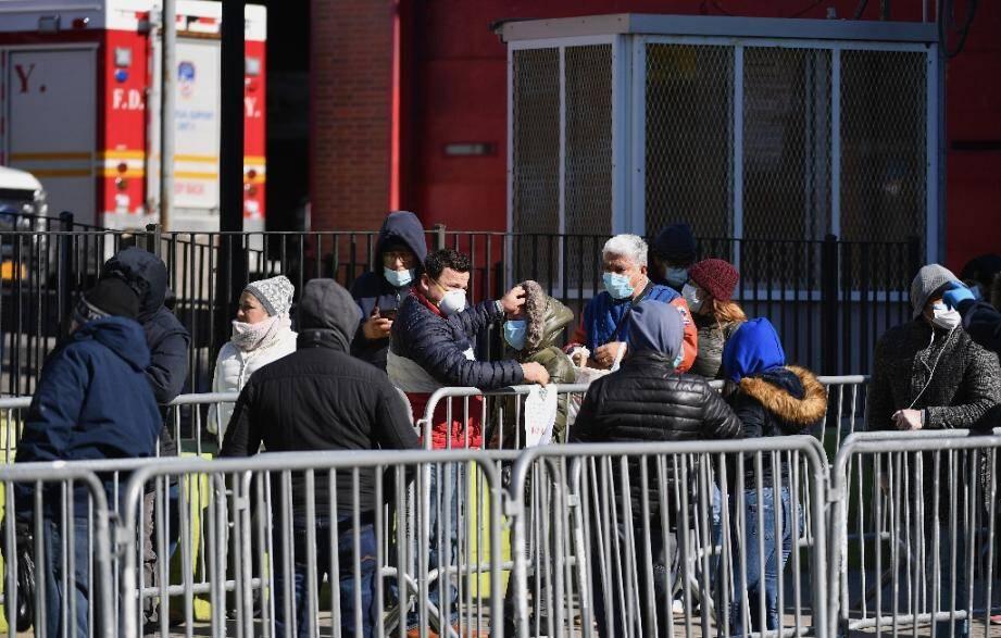 Des New-Yorkais attendent pour se soumettre au test de dépistage du coronavirus à l'hôpital d'Elmhurst, le 26 mars 2020