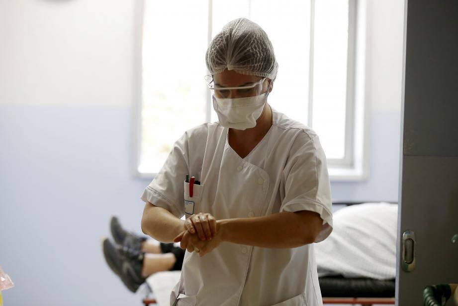 Une infirmière s'occupe d'un patient qui vient d'être testé positif au Covid-19 à l'hôpital La Palmosa à Menton.