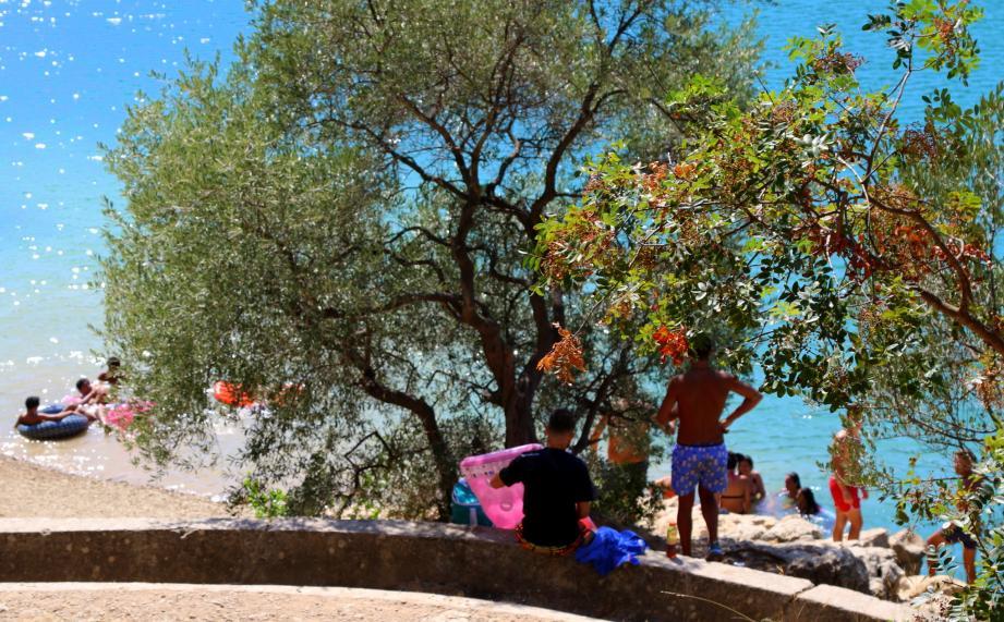 De nombreux groupes de personnes profitent de l'eau malgré les panneaux d'interdiction de la baignade.