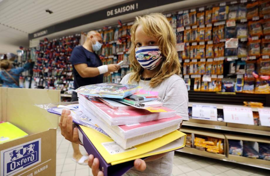 Nicole, 8 ans, s'attelle à sa tâche préférée : choisir ses cahiers et stylos pour la rentrée des classes.