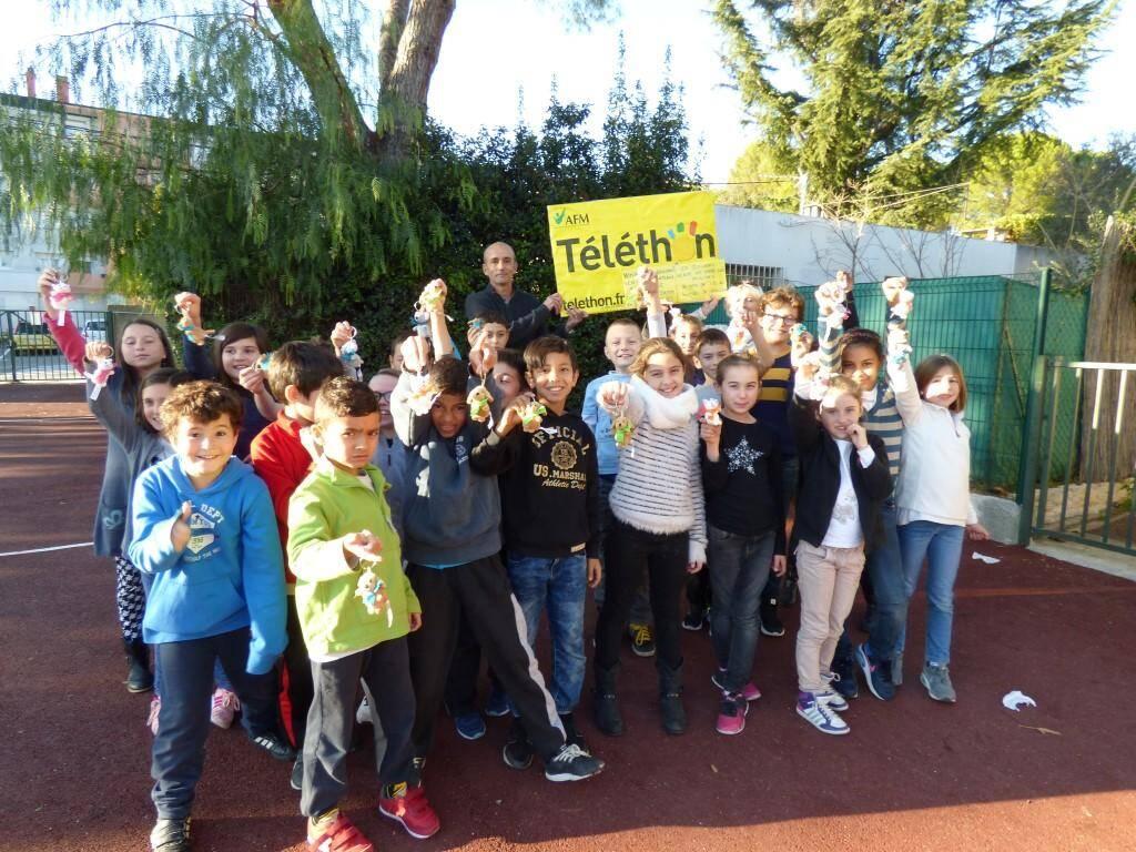Autour du directeur Dominique Brocal et de son assistante, Patricia Benoît, les enfants de l'école primaire Paul-Arène se mobilisent en proposant des peluches porte-clés au profit du Téléthon.