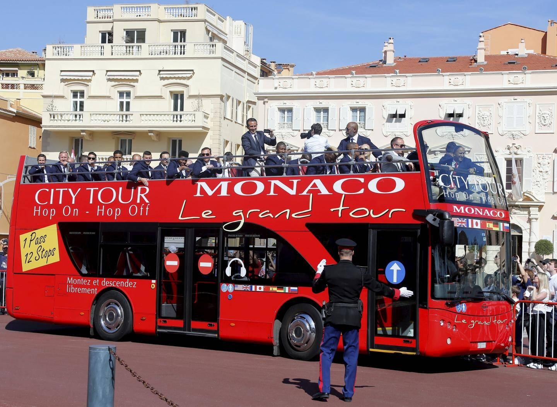 Les joueurs, partis du stade Louis-II en bus à impériale, arrivent sur la place du Palais, où ils seront reçus par le Prince.