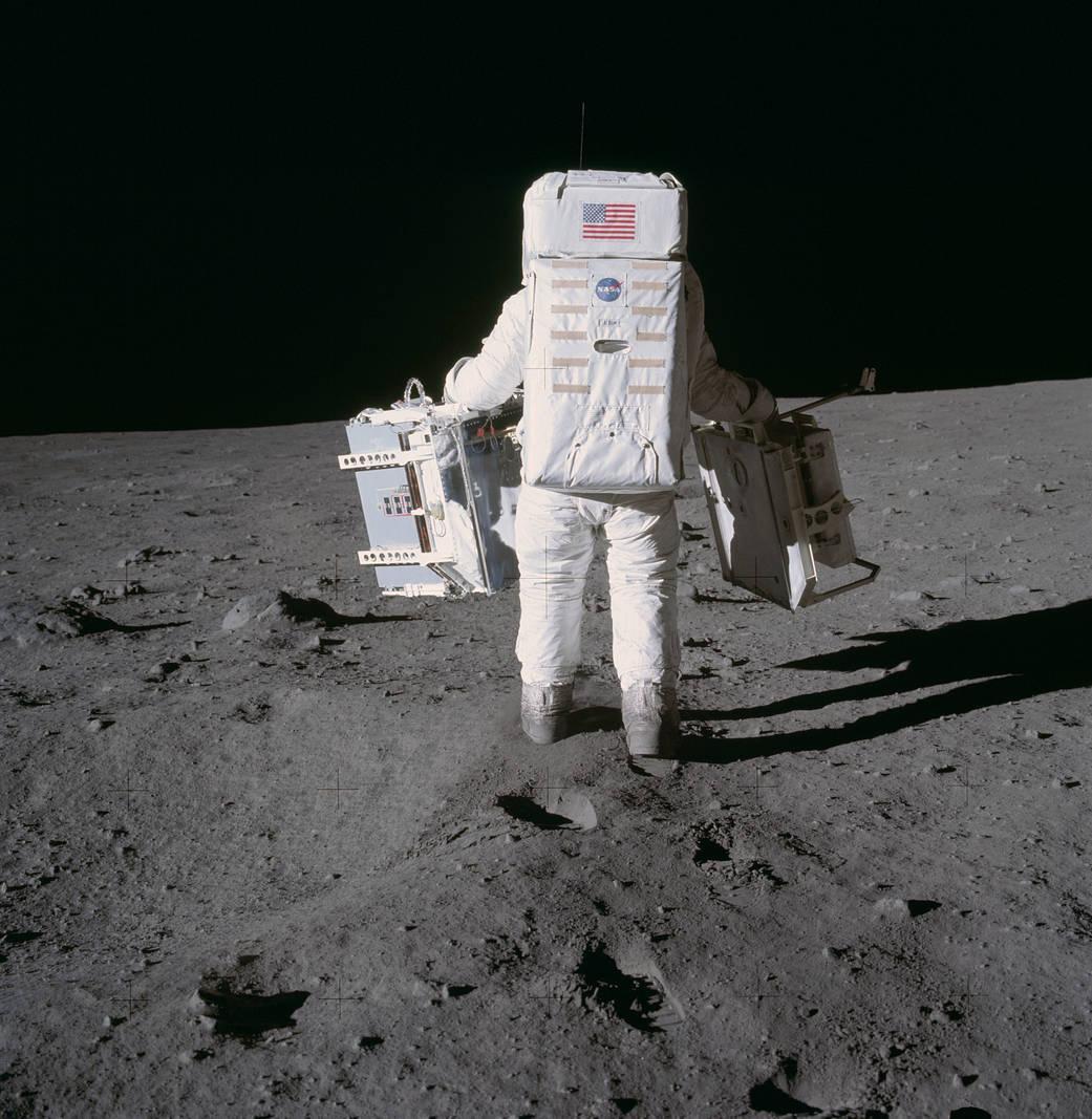 Buzz Aldrin, photographié par Neil Armstrong, porte deux appareils en vue de réaliser des expériences scientifiques sur la Lune.