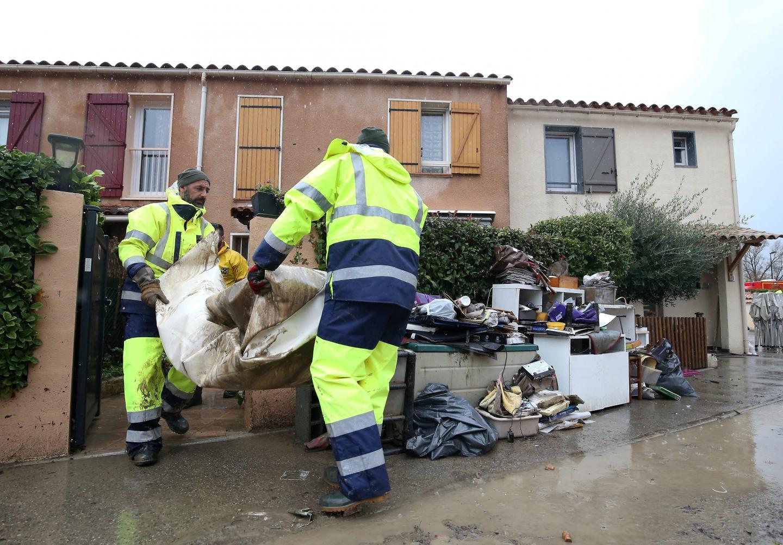 Les agents vident les objets endommagés par la boue.
