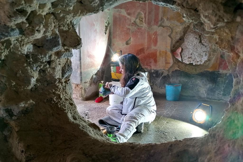Photo du 18 février 2020 montrant une restauratrice à l'oeuvre dans la maison des chastes amants sur le site archéologique de Pompéi près de Naples