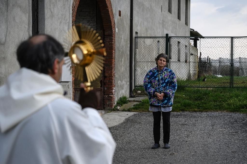 Le père Don Kresimir Busic prie avec une paroissienne à Manta, dans le Piedmont, dans le nord de l'Italie, dans le cadre d'une procession religieuse pour bénir les maisons contre le coronavirus, le 25 mars 2020