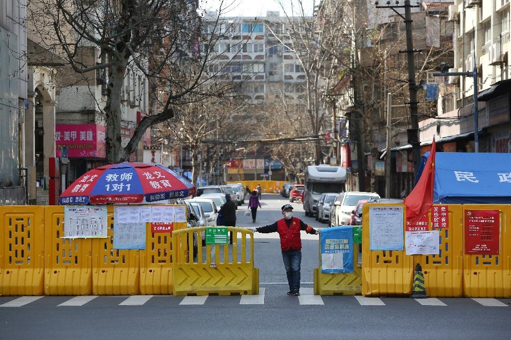 Un homme devant une barrière empêchant l'enrée dans un quartier confiné de Wuhan, le 15 mars 2020 pendant l'épidémie du nouveau coronavirus