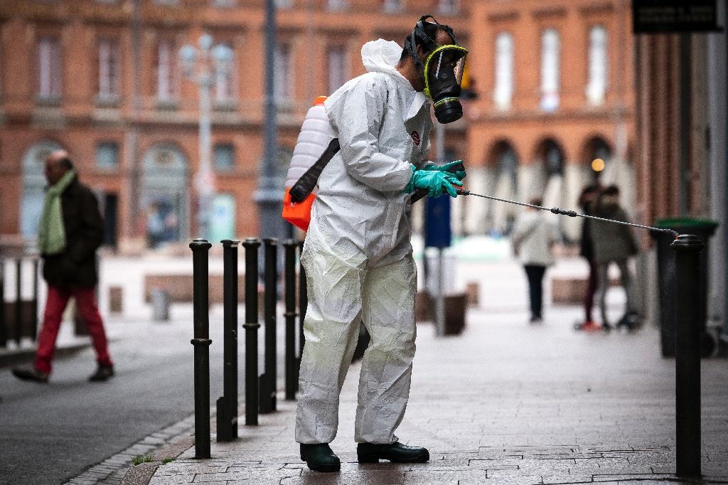 Un employé municipal en combinaison de protection désinfecte une rue de Toulouse, le 6 avril 2020 pendant l'épidémie de coronavirus