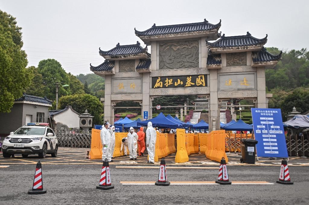 Des hommes protégés par des combinaison contrôlent l'accès au cimetière de Biandanshan à Wuhan, le 31 mars 2020