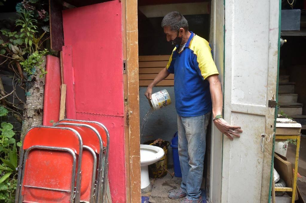 Jorge Ariza verse de l'eau dans la cuvette des toilettes de sa maison, construite de bric et de broc, le 26 mai 2020 à Bogota, en Colombie