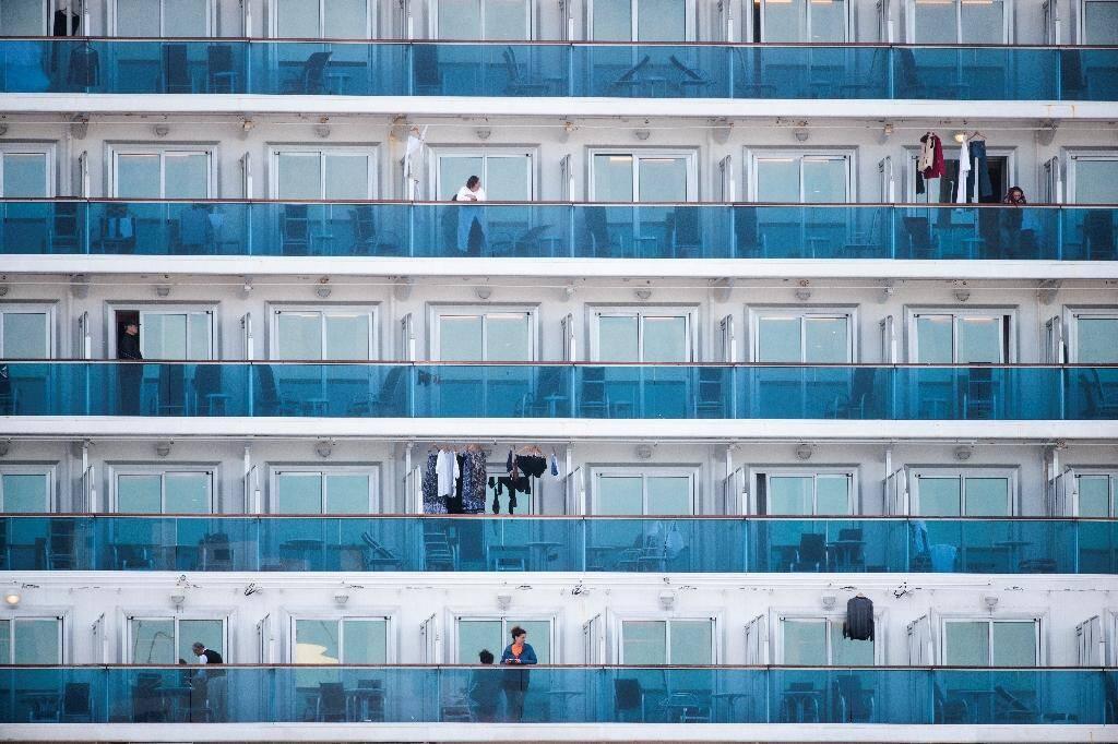 Des passagers sont aperçus sur les balcons du bateau de croisière Diamond Princess, avec environ 3.600 personnes à bord placées en quarantaine par crainte du coronavirus dans le port de Yokohama au Japon le 12 février 2020