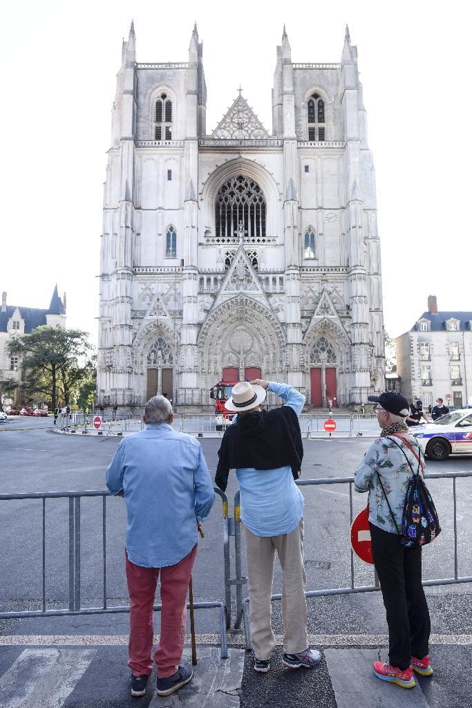 Des passants regardent la façade de la cathédrale Saint-Pierre-et-Saint-Paul de Nantes touchée par un incendie, le 19 juillet 2020