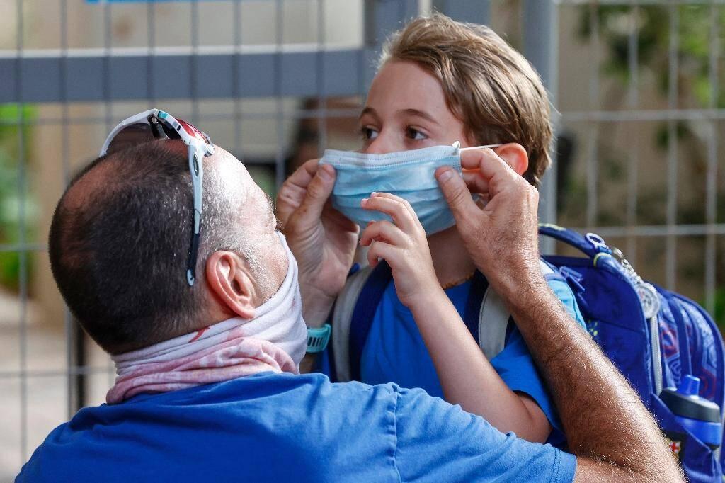 Un père ajuste le masque de sa fille le jour de la rentrée scolaire, le 1er septembre 2020 à Tel Aviv