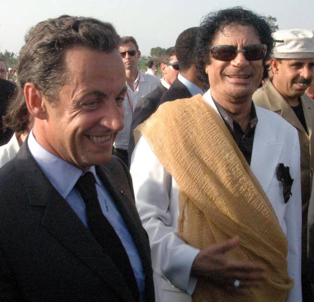 Le président Nicolas Sarkozy (g) est accueilli par le chef libyen  Mouammar Kadhafi (d) à son arrivée à Tripoli, le 25 juillet 2007