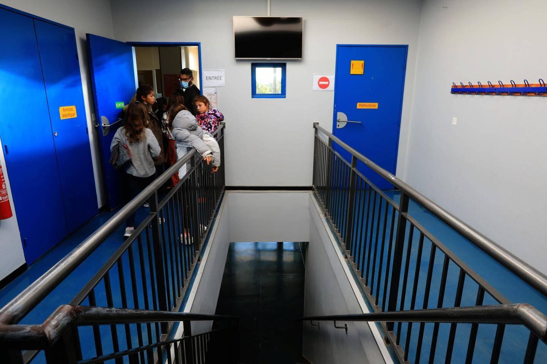 """Les écoliers entrent dans le réfectoire par groupes, après s'être lavé les mains """"avec du savon"""". Ils suivent un circuit dans tous les bâtiments pour éviter de croiser d'autres personnes. Des écriteaux sont installés partout."""