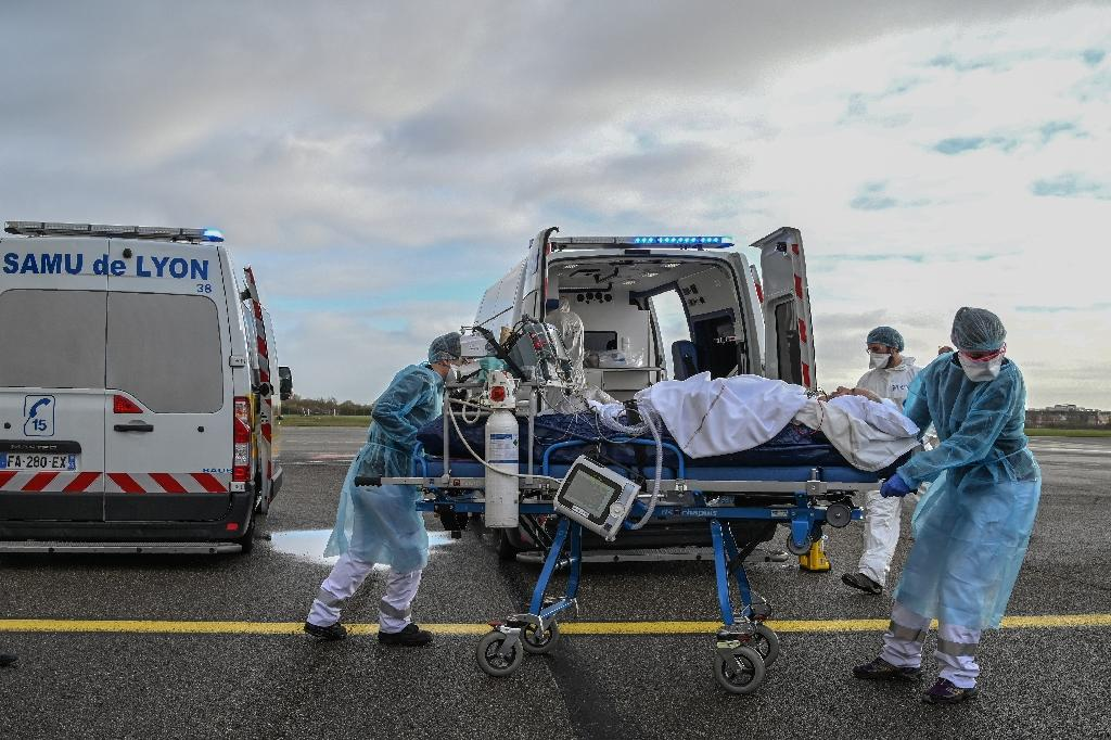 Du personnel de santé transporte un patient sur un brancard avant son évacuation vers un autre hôpital, à l'aéroport de Bron près de Lyon, en pleine épidémie de coronavirus, le 16 novembre 2020