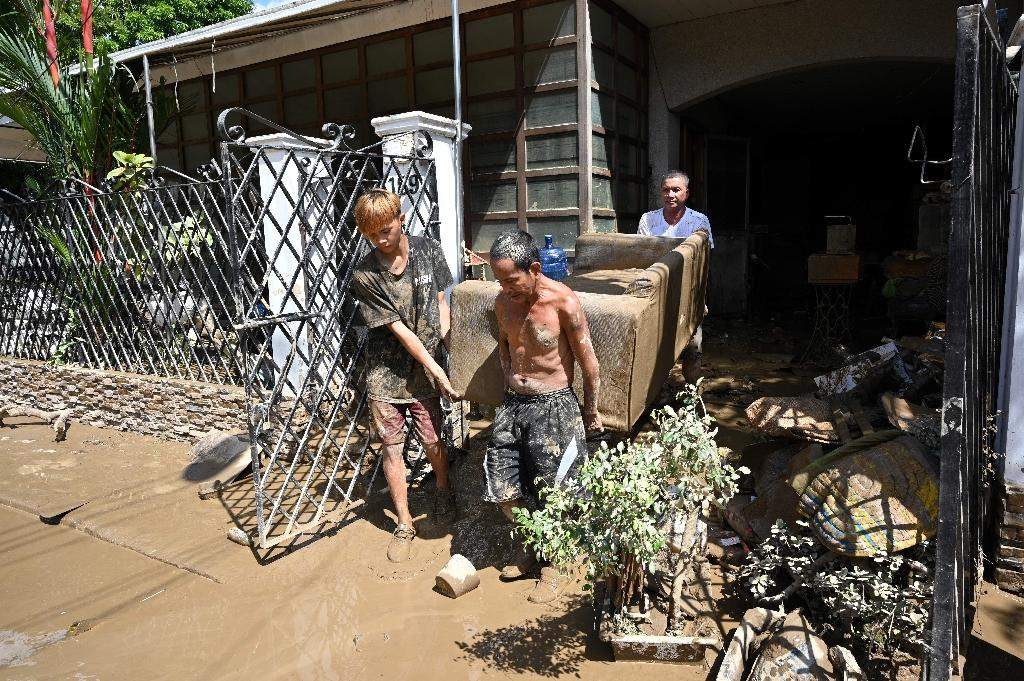 As floodwaters subsided, residents were left with the task of cleaning up the mud and destruction left behind
