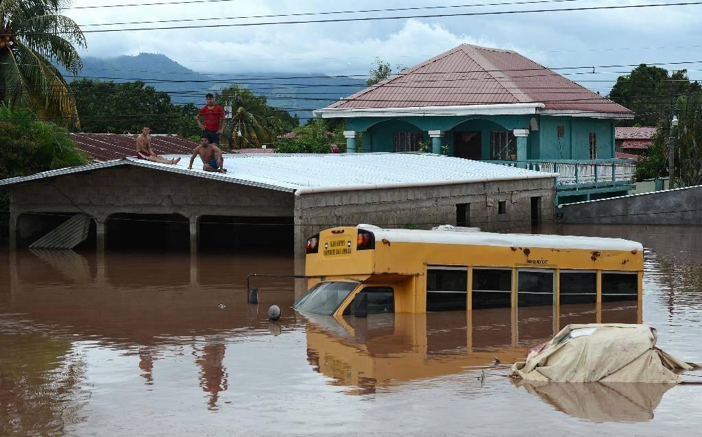 Des habitants réfugiés sur le toit d'un bâtiment près d'un bus submergé par les eaux, le 6 novembre 2020 à El Progreso, au Honduras